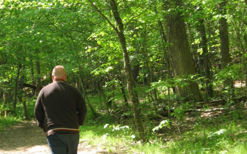 Bill Powell walks on a trail at Eno River State Park