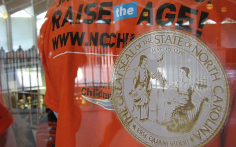 A Raise the Age supporter stands in the gallery of the NC House of Representatives in Raleigh