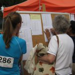 Competitors check the results board at the track and field events of the Senior Games last week in Cary.