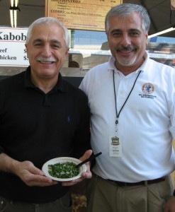 Brothers Sam and Joe Saleh, owners of Neomonde bakery, show off a tabouleh salad they're selling at the State Fair.