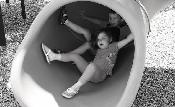 Kids sliding down a tube slide