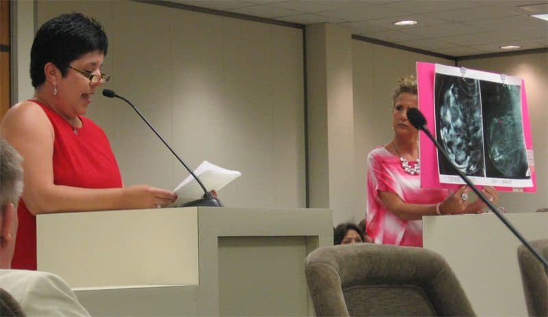 Breast density awareness advocate Gina Waters (r) holds up mammography images of breasts as Addy Jeffrey (l), testifies to the Senate Health Committee about her experience being diagnosed with dense breasts and breast cancer.