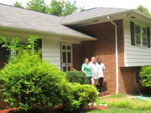 Jenny Gadd, Alex Harrison and Jemel Sutton stand in front of the group home where Harrison lives and Sutton works.