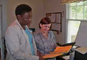 Family court administrator Sanya Eller (left) and Safe Havens director Debbie Norman (right) review Tuesday's schedule.