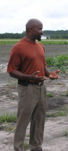 Conetoe  minister Richard Joyner shows visitors around the community garden.