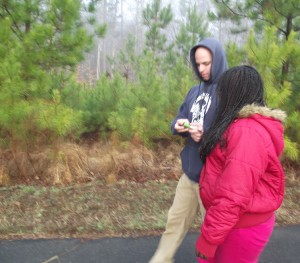 Classroom assistant Tyler Mintzer helps a student from Scroggs Elementary School reset her player during a recent morning walk.