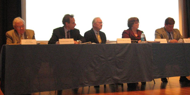 Members of the Medicaid Reform Advisory Group listen to speakers during the meeting Wednesday. L to R: Sen. Louis Pate, Richard Gilbert, MD, Dennis Barry (chair), Peggy Terhune, PhD, Rep. Nelson Dollar. Photo credit: Rose Hoban