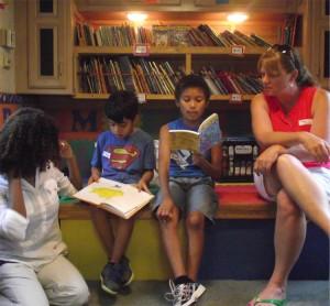 Volunteers help children read their books in the Read and Feed van.
