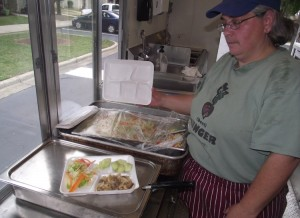 A volunteer from InterFaith Food Shuttle shows off the day's offering of beef stroganoff, salad and melon