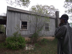 Graham Cotton shows the back of his house, where a kitchen fire last winter destroyed part of the structure.