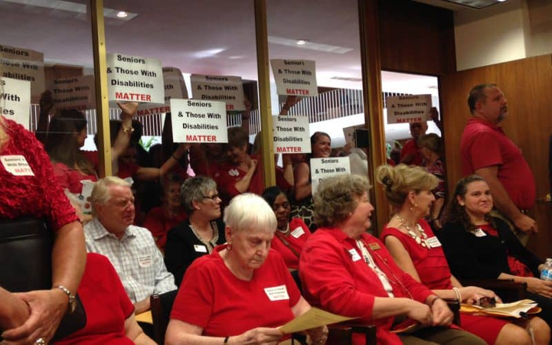 Seniors and people with disabilities and their advocates all wore red at the General Assembly Tuesday to show their displeasure at Medicaid cuts in the Senate budget.