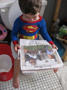 Little boy on toilet, reading the newspaper.