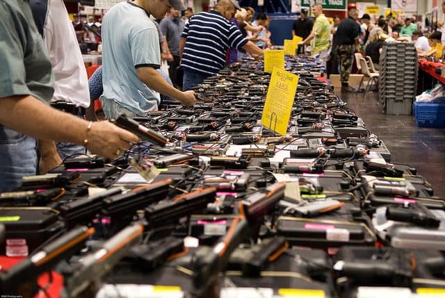 photo of a table at a gun show covered with firearms