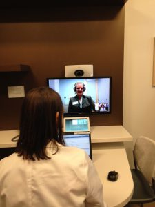 A health care provider speaks to a patient over a closed circuit video feed using a web cam and monitor.