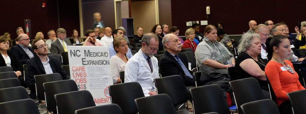 Dr. Gary Greenberg (white coat), who practices at Urban Ministries of Wake County, prepares his statement as the crowd listens to HHS Sec. Rick Brajer give a presentation on the draft Medicaid proposal.