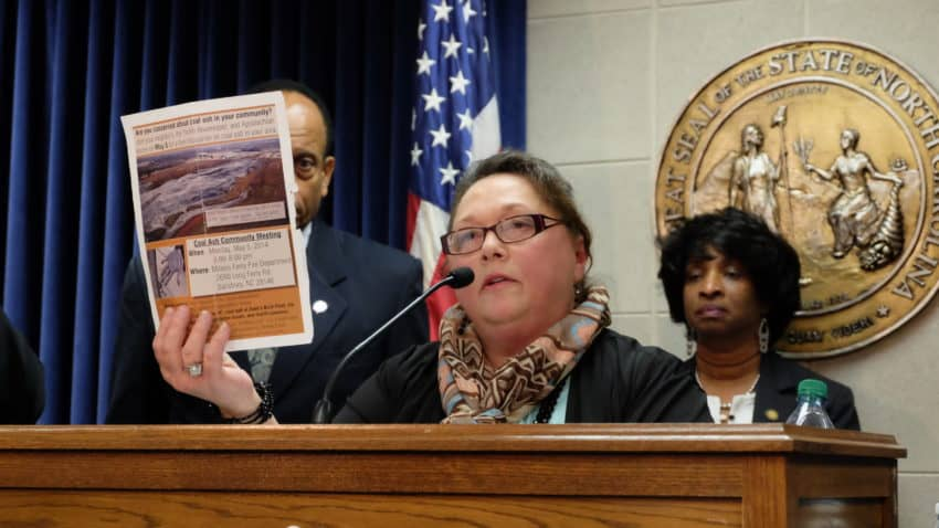 Well owner Deborah Graham holds up a photograph of the coal ash pit that's several hundred yards from her home in Salisbury while at a press conference at the General Assembly in Raleigh. Photo credit: Rose Hoban