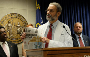 Reidsville physician Stephen Luking holds up his open letter urging Medicaid expansion which was published in the Greensboro News & Record in April.
