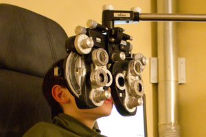 Boy at phoropter; The phoropter is the most recognizable tool used by optometrists, used to determine a person's eyeglass prescription.