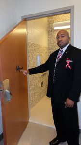 Cherry staffer Joe Brown shows how bathroom doors are designed to prevent a patient from hanging themselves: Doors are cut at an angle and hooks for towels are flexible.