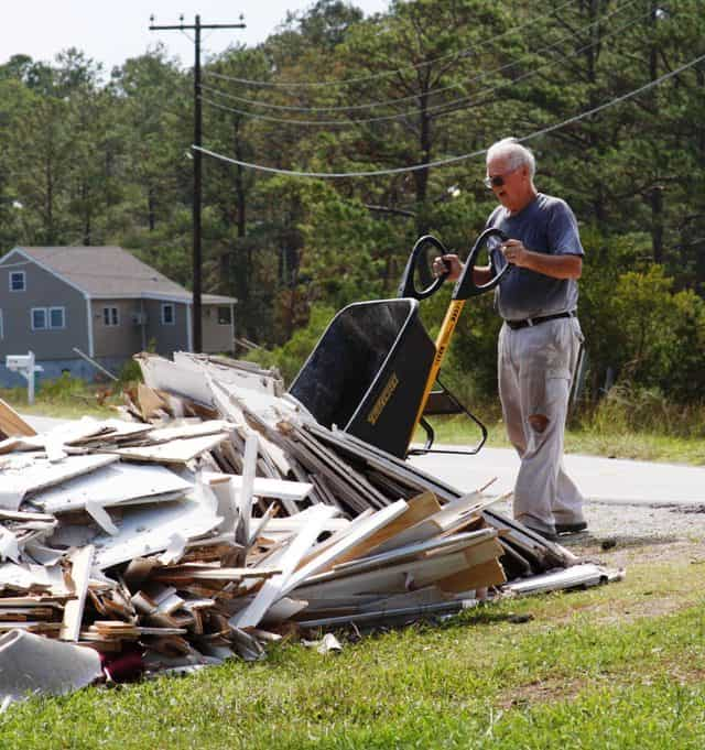 Man dumping debris from a wheelbarrow onto a large refuse pile. After flooding from Hurricane Irene in 2011, some North Carolinians had a big clean up on their hands. Sea Level, NC, Sep 7 2011 --Flood damage from Hurricane Irene. FEMA photo/Tim Burkitt