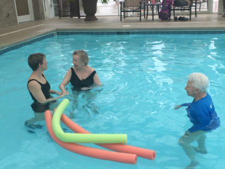 Volunteer trainer Allison Bailey, left, works with Sandy Kirkland, center, and Pat Frew, during an aquatics exercise class at Woodland Terrace assisted living center in Cary.