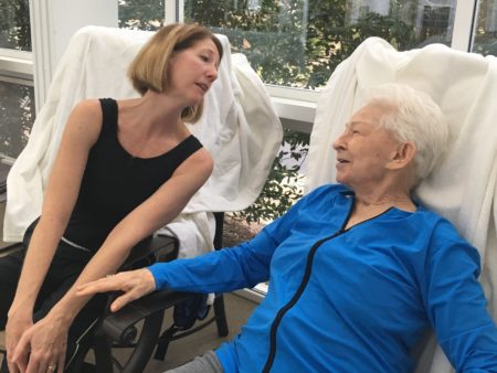 Michele Cox, assistant activities director at Woodland Terrace, encourages resident Pat Frew to enter the swimming pool for aquatics exercise class. Photograph by Thomas Goldsmith