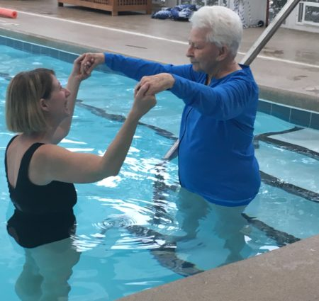 Woodland Terrace assistant activities director Michele Cox helps as resident Pat Frew gets into the swimming pool for aquatics exercise class. Photograph by Thomas Goldsmith
