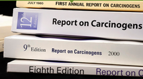 Photo of a pile of books/ reports titled: Report on Carcinogens. In 1978, Congress mandated that the Secretary of the US Dept. of Health and Human Services publish a science-based, public health report that identifies agents, substances, mixtures, or exposures in our environment that pose a hazard to people.