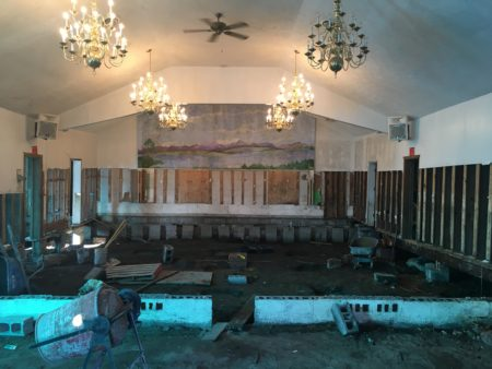 photo shows interoir of church, all of the wall board has been removed, floor removed, and the dirt underfloor is revealed