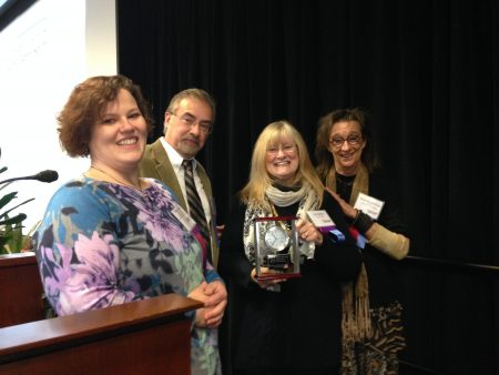 Photo shows four people smiling at the camera. Julie Bailey holds up a clock.