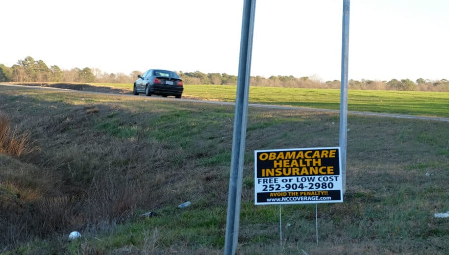 Sign at a lonely crossroads advertising Obamacare