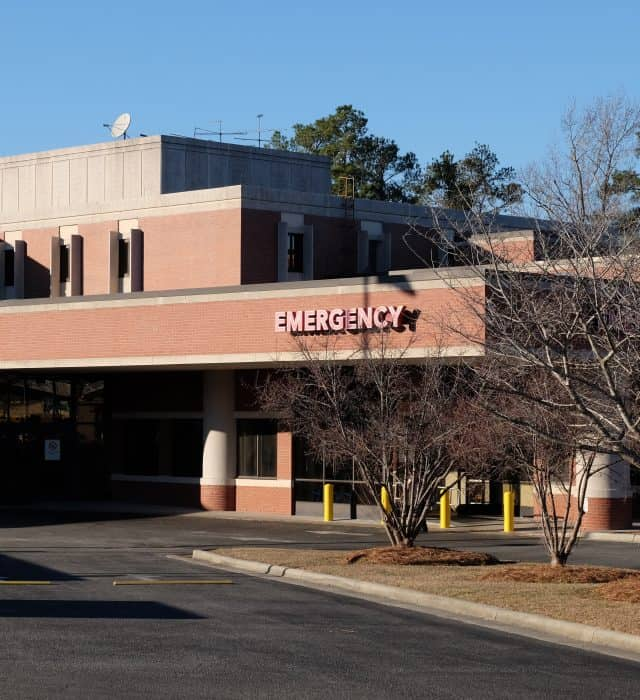 """Generic emergency department entrance photo, with a carport and sign saying """"Emergency"""" No hospital name is visible."""