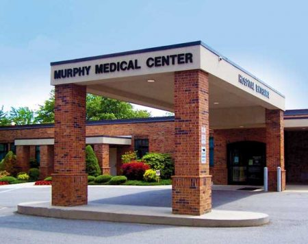 "Photo shows the carport of the hospital with the name, Murphy MEdical Center"" above the entrance."