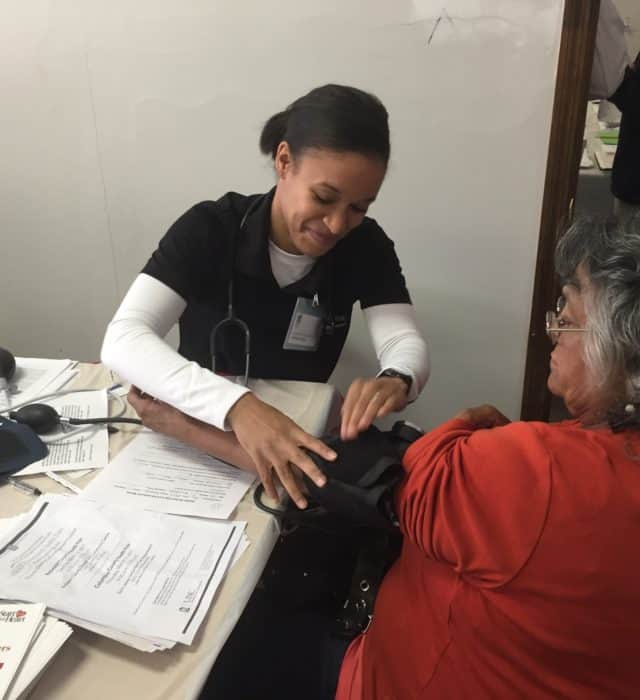 a young woman takes an older woman's blood pressure
