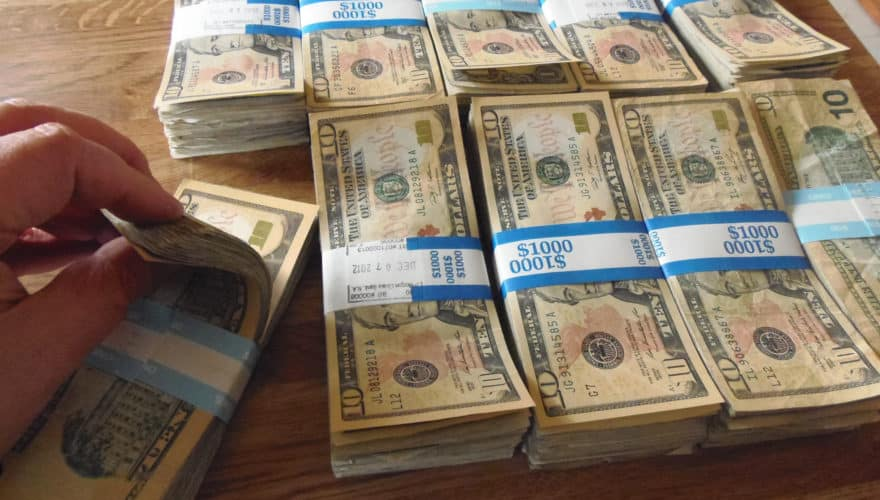 picture of stacks of money, hands counts one stack.