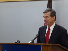 photo shows cooper at a podium, he's wearing a suit and a red tie