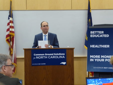 "shows Perusse standing at a podium next to a poster that reads: ""Better Educated, Healthier, More money in your pocket"""