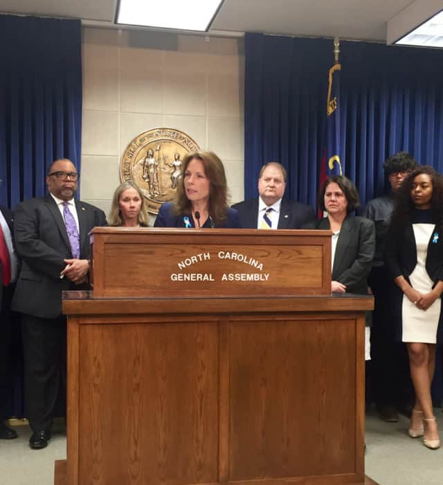 Sen Barringer stands at podium with crowd of serious looking people beside and behind her.