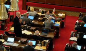 Man stands with a microphone among legislator desks. Some appear to be listening, others are reading or looking at their computers.