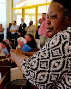 African American woman watches the debate. She's sitting among a large crowd of white observers.