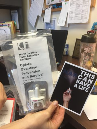 a pair of hands holds several bags containing literature and one containing a nasal applicator for naloxone. One of the pieces of literature reads: Opioid Overdose Prevention and Survival