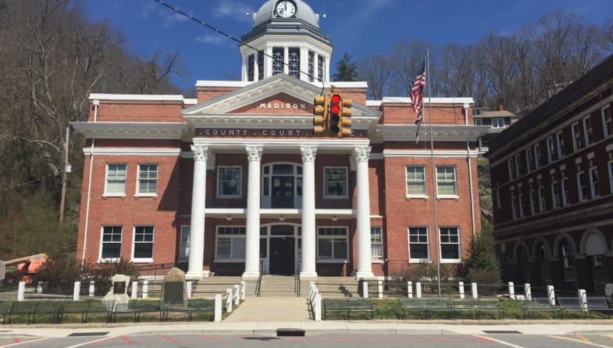 photo shows the madison county courthouse, an old brick building with tall white columns and a gazebo on top