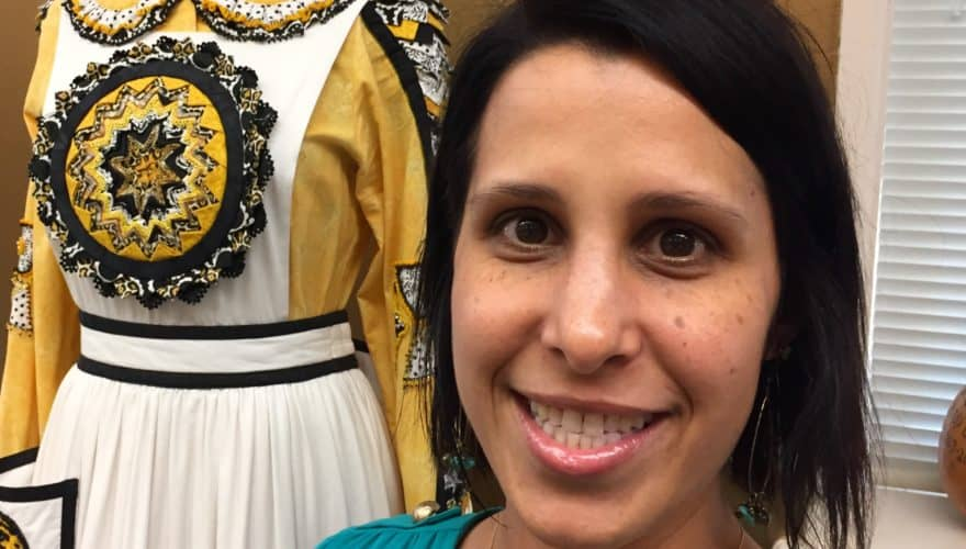 smiling woman standing in front of a mannekin displaying a traditional dress with intricate beading
