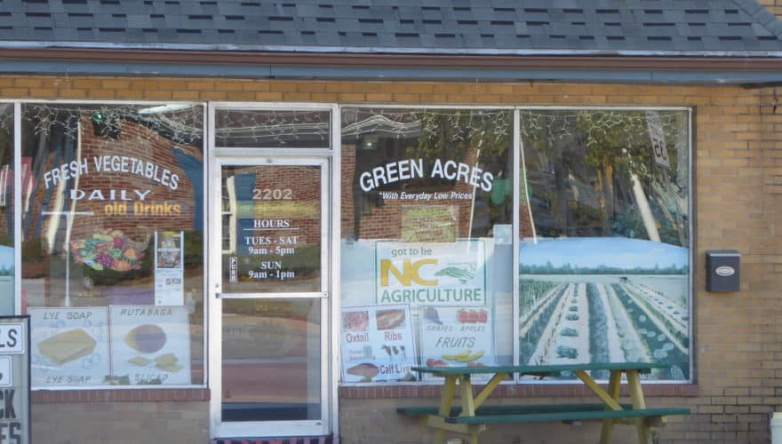 """photo shows the front of a small store advertising fruits and vegetables and """"got to be NC Agriculture"""" signs"""