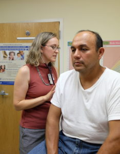 a female physician checks the lungs of a male patient.