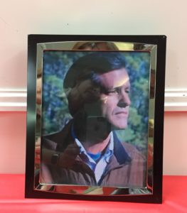 shows a framed photograph of a man, sitting on a table.