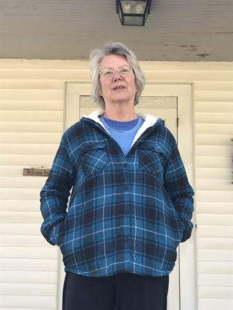 woman stands on her porch, wearing a plaid jacket and sweatshirt