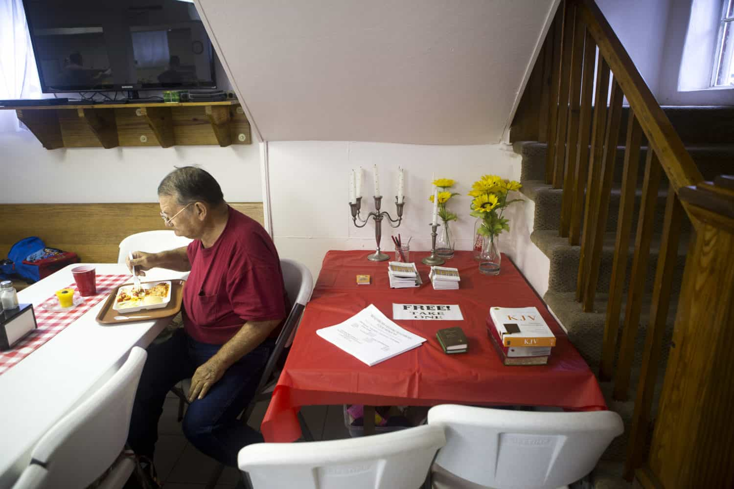 a man experiencing food insecurity sits eating a a meal in a takeout container