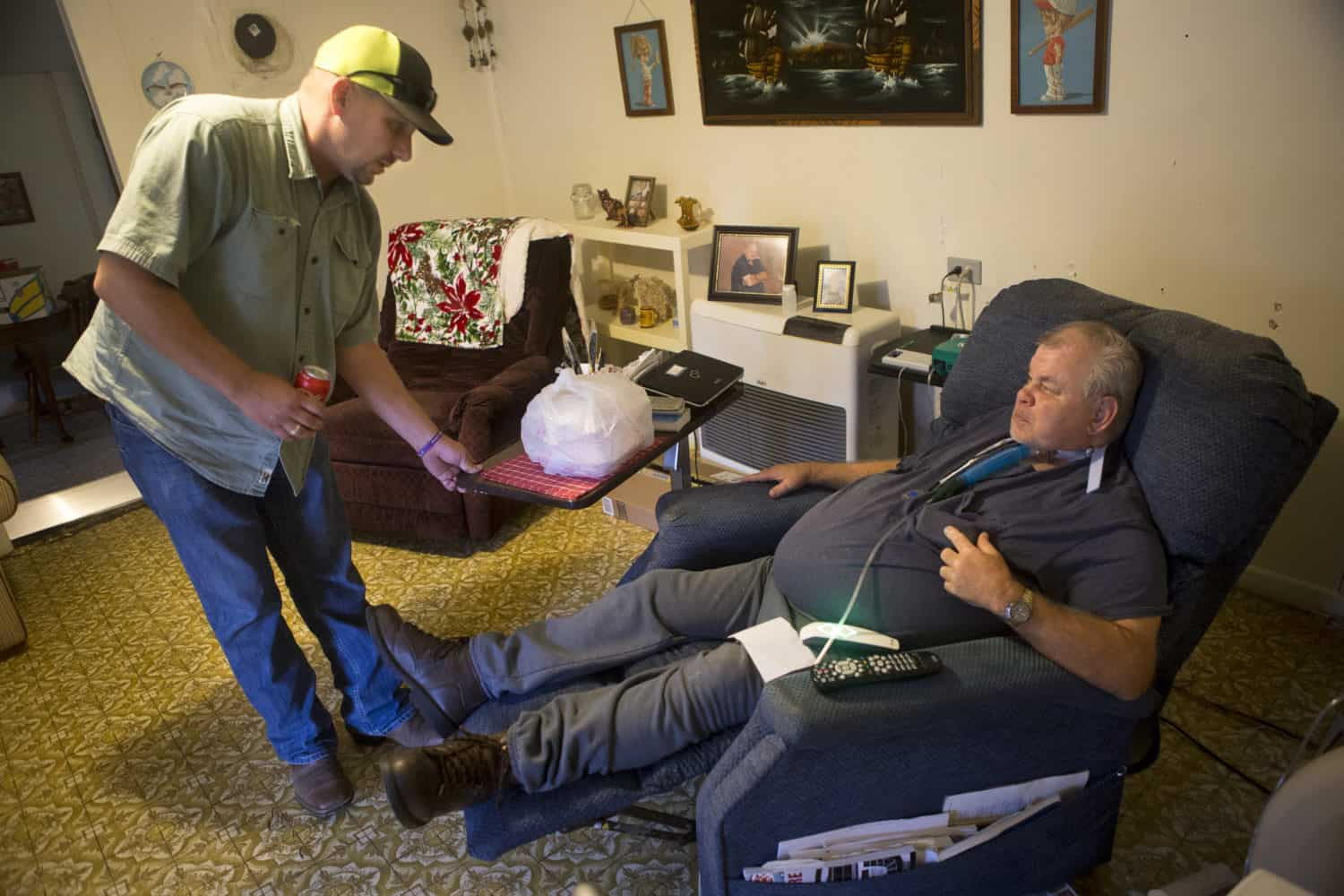 On man brings food to another man who's sitting in a lounger chair tethered to an oxygen tank. The second may is experiencing food insecurity.