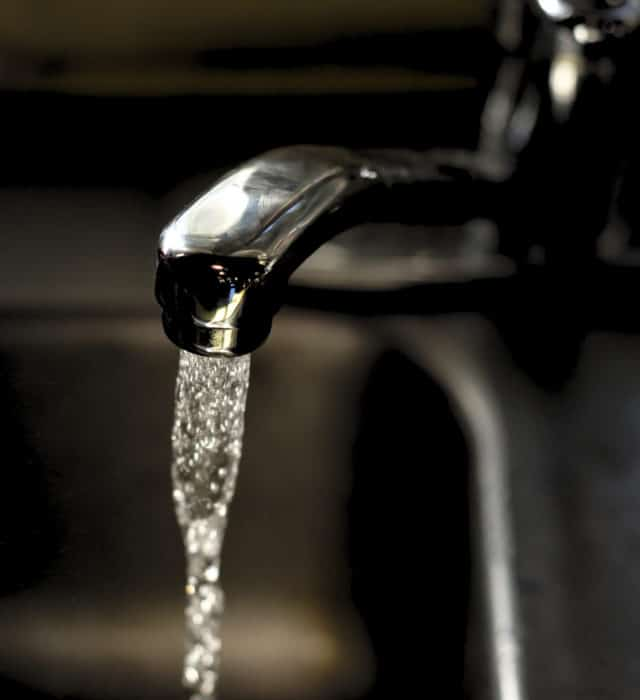 A faucet with water flowing from it, as an illustration for drinking water contamination, with substances such as 1,4 dioxane and PFAS